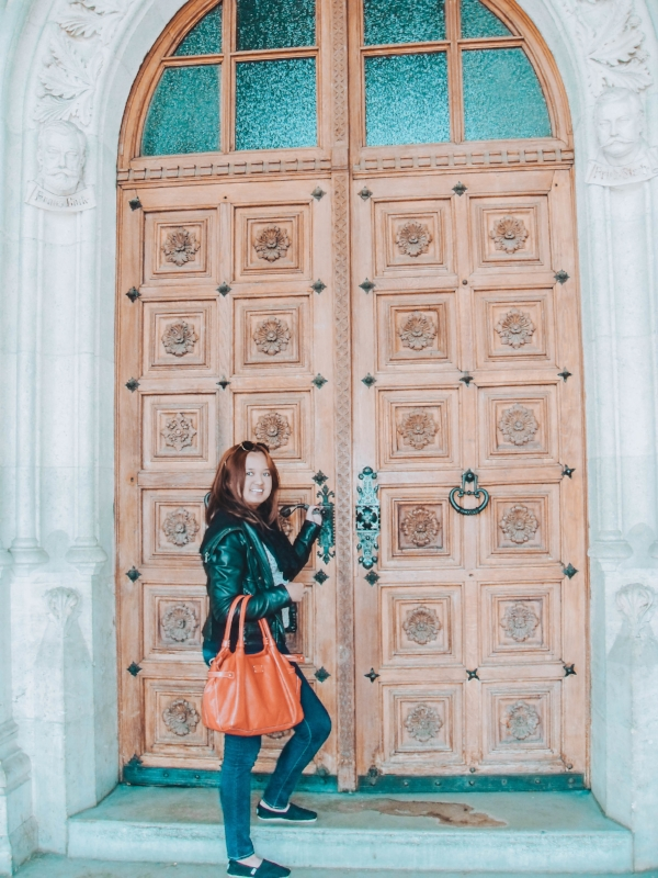Traveling the world alone opens doors to a lot of opportunities, as there is a lot to gain in this experience. I am pictured in front of a door at Wiener Rathaus (Vienna City Hall) in Vienna, Austria.