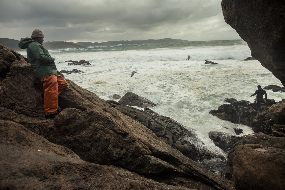 "December 16, 2011 - Laxe (La Coruña). ""Feuto"" - a retired percebeiros - observes his son finding his way on the cliff. He can't stay home when the sea is in bad conditions and he stays all the time with his son. © Thomas Cristofoletti 2011"