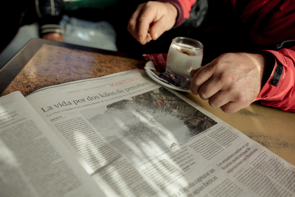 "December 17, 2011 - Laxe (La Coruña). Julio reads an article on the local newspaper about the percebeiros dealing with the bad conditions of the sea of the previous days. The title says ""Risking the life for 2 kg of percebes"". © Thomas Cristofoletti 2011"
