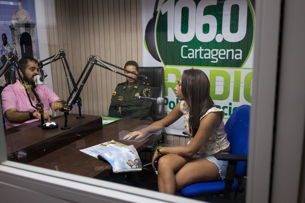 "CARTAGENA, COLOMBIA - FEBRUARY 25, 2015: Wilson Castañeda, director of the LGBT rights group Caribe Afirmativo, and the trans activist Tania Duarte participate in a weekly radio program hosted by the police in Cartageña, Colombia. Each Friday, members of Caribe Afirmativo discuss on air the issues faced by the LGBT community in Colombia's Caribbean region on a program heard by around 80,000 listeners. ""We talk about marriage equality, we talk about same-sex adoption, we talk about the sexual transmission of disease. We touch upon many topics, but not only those that affect us, but also affect the community in general,"" says Duarte, a 23-year-old philosophy major. Throughout Colombia's Caribbean region, Caribe Afirmativo works to transform the way the society views and treats LGBT individuals. ""The impact of Caribe Afirmativo is that before, here in Colombia's Caribbean Coast, no one was talking about sexual diversity. No one was talking about gender identity. No one was talking about human rights reports. There were no data, there was no follow up. We were invisible people who, if we existed, only existed on TV,"" says Duarte, who is the only trans person studying at Cartagena University. Castañeda explains that the trans population in the Colombian Caribbean faces the most danger of any segment of the LGBT community: ""Of the 119 murders [of LGBT members] in the past seven years, 70 percent were of trans persons."" Throughout Latin America and the Caribbean and around the world, USAID works side by side with groups like Caribe Afirmativo to support human rights and dignity."
