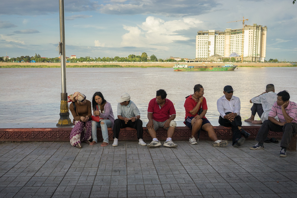 "July 13, 2014 - Phnom Penh. Champa talks with a sex worker and a group of clients along the riverside of Phnom Penh, one of the places frequented by tourists and ""sexpats"" of the capital. At the age of 42 years, Champa works for the Women's Network for Unity, an organization that helps Cambodian sex-workers and transgender people. She spends many of her evenings talking and educating them about safe sex. © Thomas Cristofoletti / Ruom"