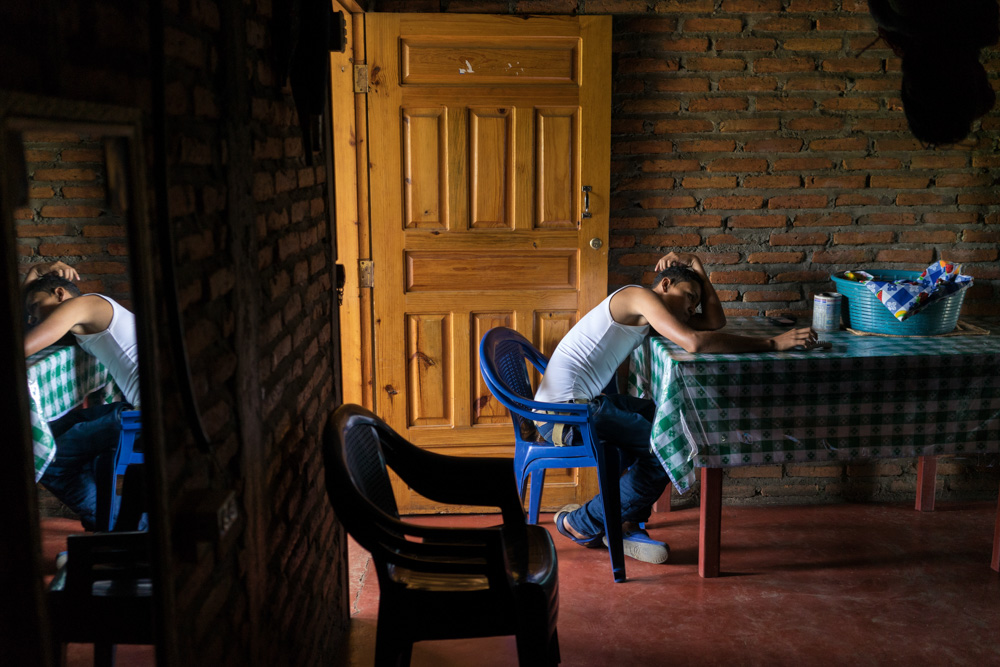June 23, 2015 - Tegucigalpa (Honduras). Luis Edgardo Cruz Diaz, 15, has a moment of relax at his home in the Nueva Capital neighborhood. Just a year ago, Luis was having trouble at home and he searched for love and acceptance in the wrong places -- eventually becoming leader of the local gang. But after Luis and his family began the USAID pilot program Proponte, his counselor Sabina helped him gradually change his attitude. He left the gang, returned to school, formed positive friendships, and started respecting his mom, stepfather and siblings. © Thomas Cristofoletti / Ruom for USAID