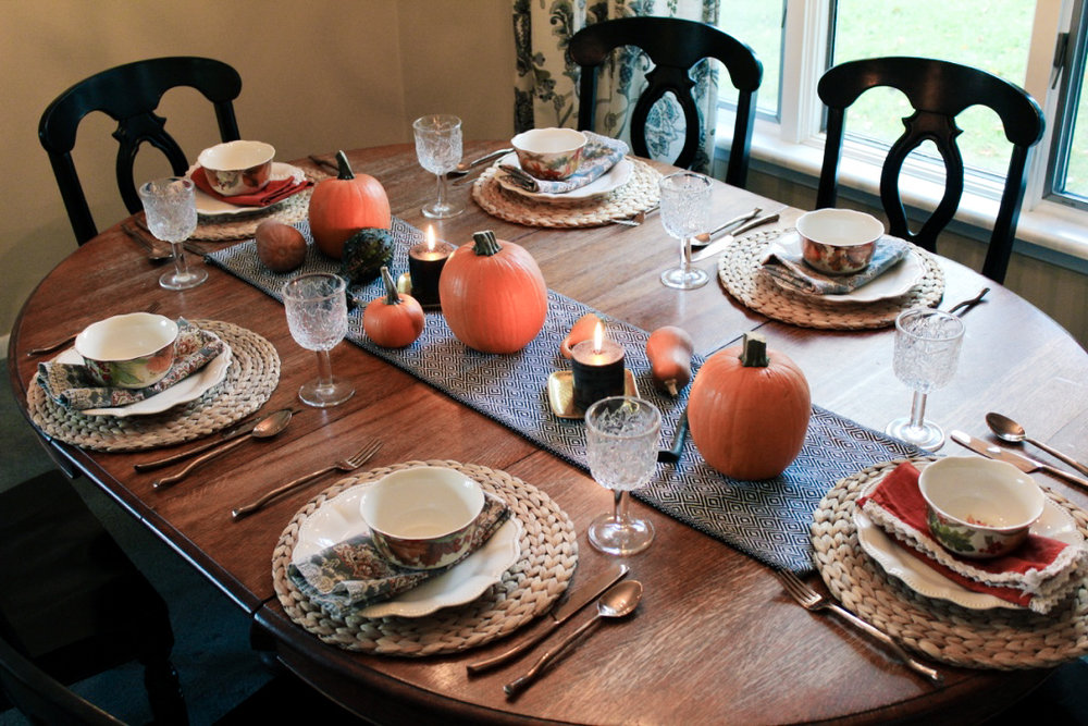 Fall harvest tablescape—table runner & placemats from Ikea, plates from Pioneer Woman (Walmart), print napkins and silverware from World Market, bowls and burnt orange napkins from HomeGoods.