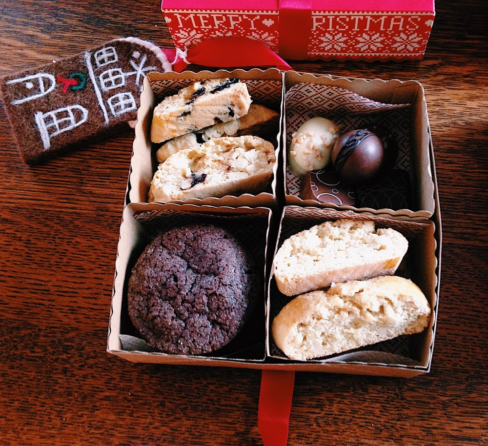 Homemade sweet treats & chocolates for gifting. Cherry walnut biscotti, almond biscotti, truffles, and dark chocolate cookies, tied with a ribbon and topped with an ornament.