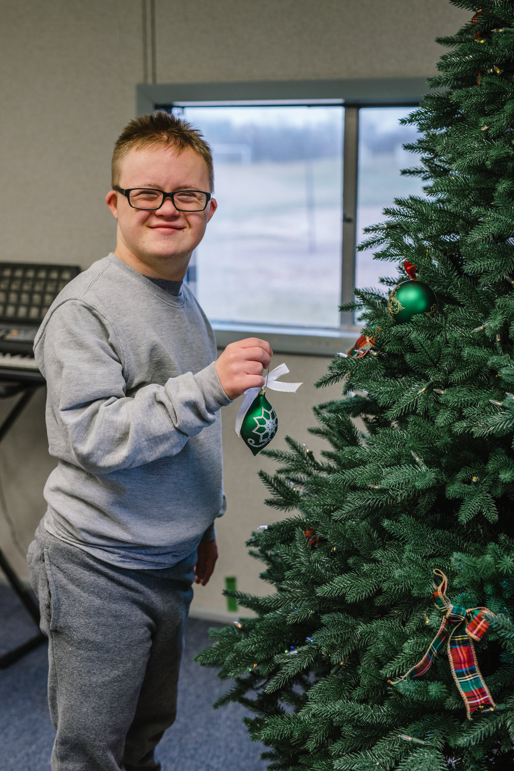 SPARC  student, Sam, decorating the tree. Photography by Rachel Cuthbert Photography.