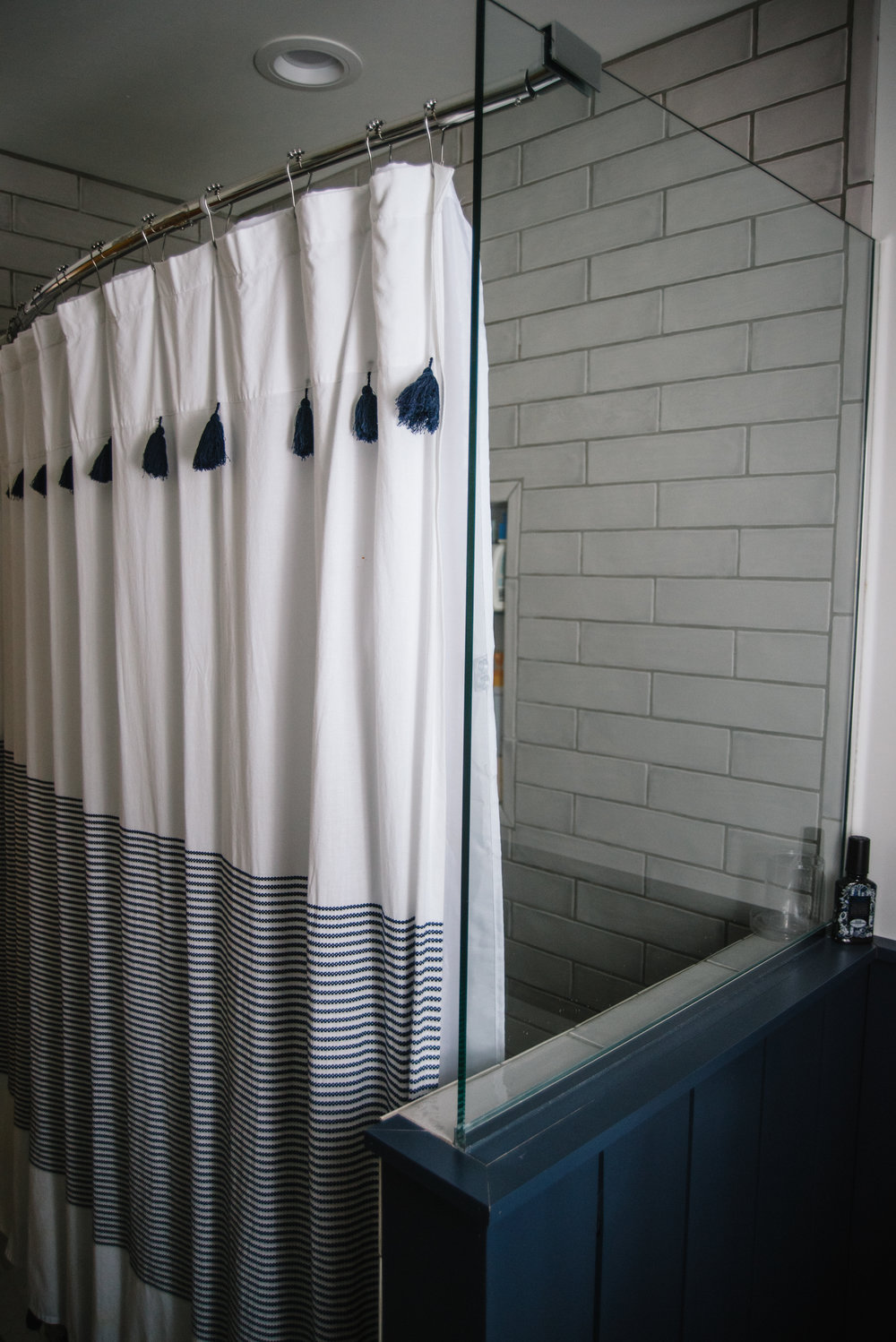 Newly renovated bath/shower with tempered glass wall..  Shower curtain by Peri Home, bloomingdales .  3x12 Retro Perla gray Tile via the Tile shop . Photo via Rachel Cuthbert Photography