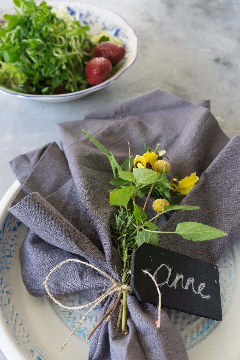 Tie your napkins with twine, herbs and pretty flowers. Personalise each one with a name tag. Chalk board name tags from Hot Dollar or craft stores.