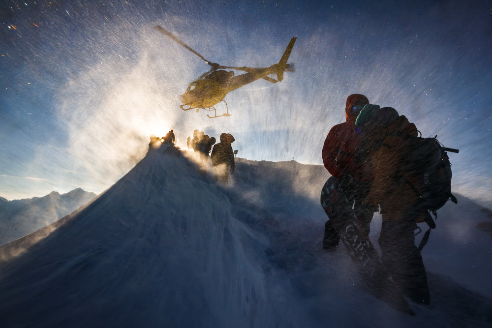 Technical staff take shelter as a helicopter takes off prior to the Nendaz Freeride ski and snowboard competition, a Freeride World Tour Qualifier (FWQ) event, on the Mont Gond in Nendaz, Switzerland, Wednesday March 21, 2018. (KEYSTONE/Valentin Flauraud)