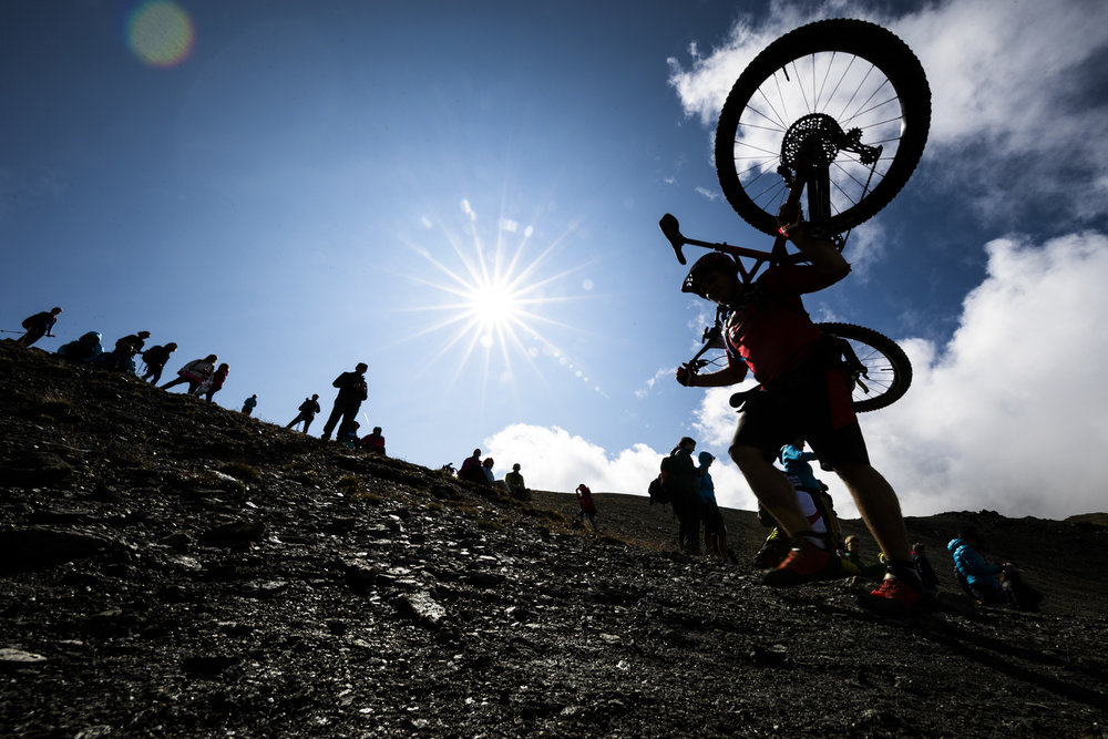 """A rider carries his bike on the """"Pas de Lona"""" during the 28th Swiss Mountain Bike Marathon """"Grand Raid"""" from Verbier to Grimentz, Southwestern Switzerland, Saturday August 19, 2017. Over 2000 mountain bikers took the start in different categories with the longest one stretching over 125 kilometers in length and 5025 meters of overall ascent. (KEYSTONE/Valentin Flauraud)"""