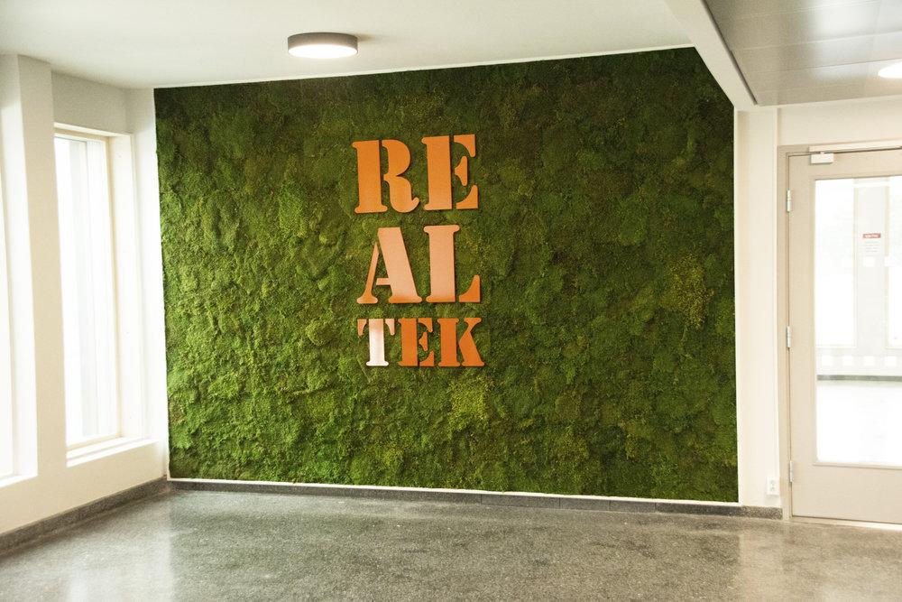Mosevegg med navnet på fakultetet som holder til på TF, Realtek