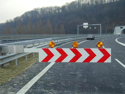 Barrières avancées - Ces installations servent à modifier rapidement un régime de circulation par l'ouverture des passages sur bande médiane des deux côtés de tunnels autoroutiers. Le trafic ainsi établi est bidirectionnel dans un tube alors que l'autre est sécurisé pour des travaux d'entretien.En cas de déviation de trafic, il doit d'abord être réduit en amont sur une voie de roulement. Nous avons développé pour ce besoin une barrière courte à monter sur les glissières fixes ou autonomes. On peut ainsi renoncer à l'immobilisation d'un véhicule pour cette signalisation.