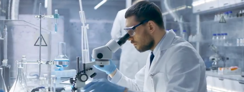 man looks at microscope.png