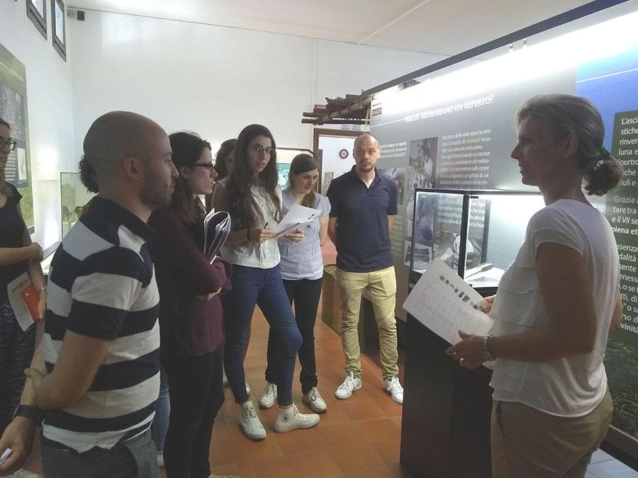 La conservatrice del Museo, Emanuela Gilli, mostra agli studenti di Makars Summer School, il reperto da scansionare: l'ascia metallica.