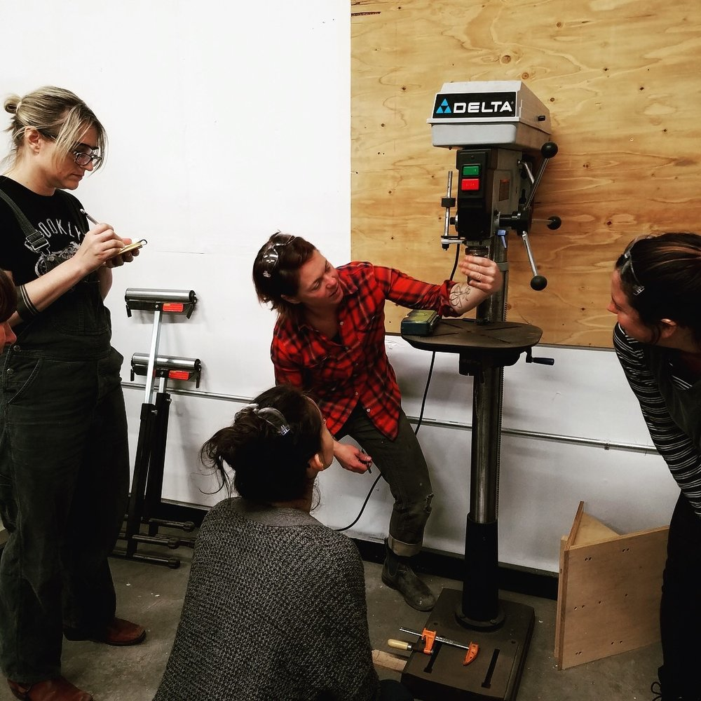 Students learning about the drill press. Photo credit Anne Marie Goco