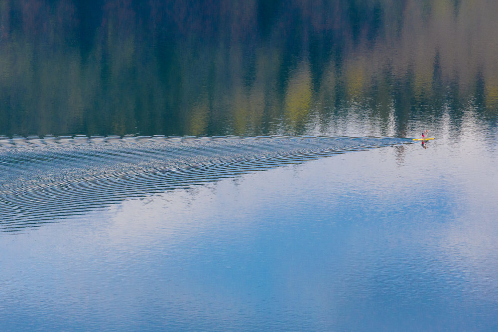 Ripples and reflections behind a stand-up paddle boarder