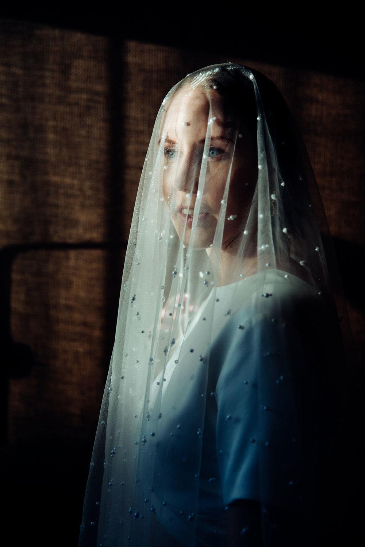 Estelle wears,  Prea James Bridal Cara gown  and  Pearl Veil ,  Brie Leon Enlazar Earrings in gold