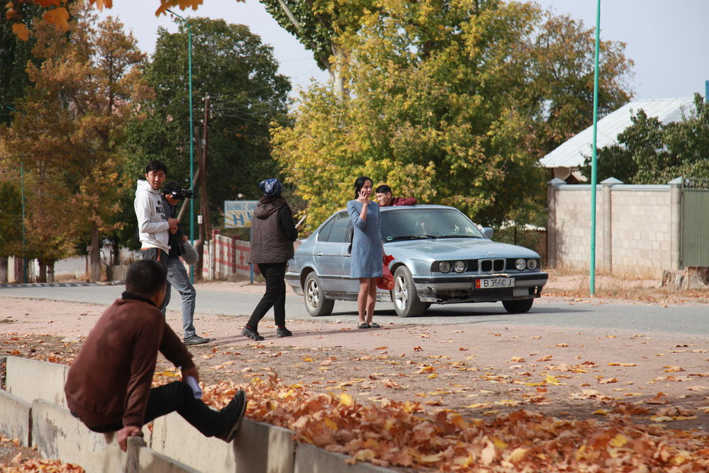 On set: Mira, played by Anara Taalaybek Kyzy, talks on the phone as a car draws up behind her