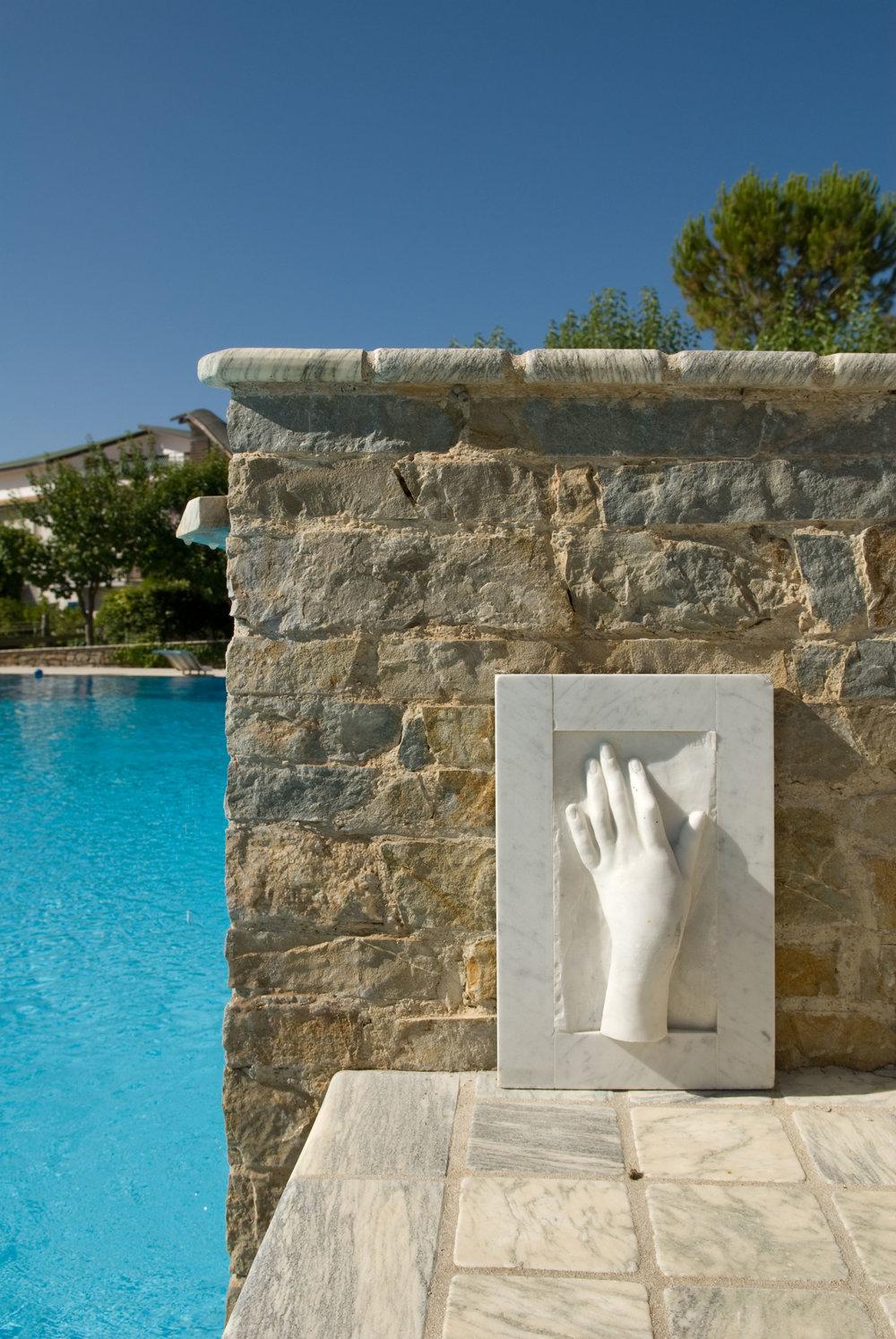 Muro in pietra e scultura in marmo bianco