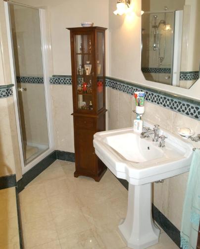 Pavimento e rivestimento bagno in Botticino e marmo verde Guatemala