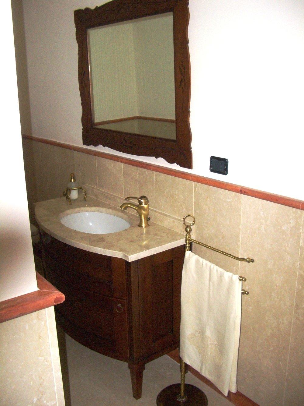 Rivestimento bagno in Botticino e pietra Travertino rosso
