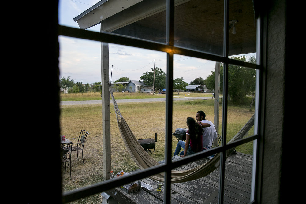 Ruben Gonzalez and his daughter sit on the front porch of their home.