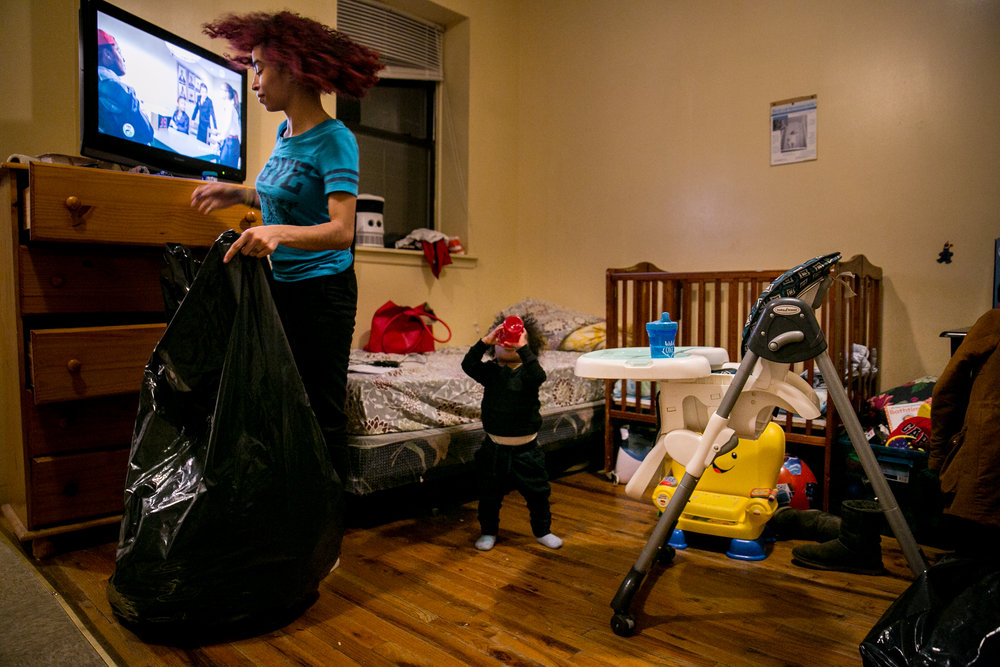 Madelyn Brito packs up her belongings alongside her 1-year-old son Cameron the night before moving out of the Kingston Family Residence homeless shelter in Brooklyn, New York