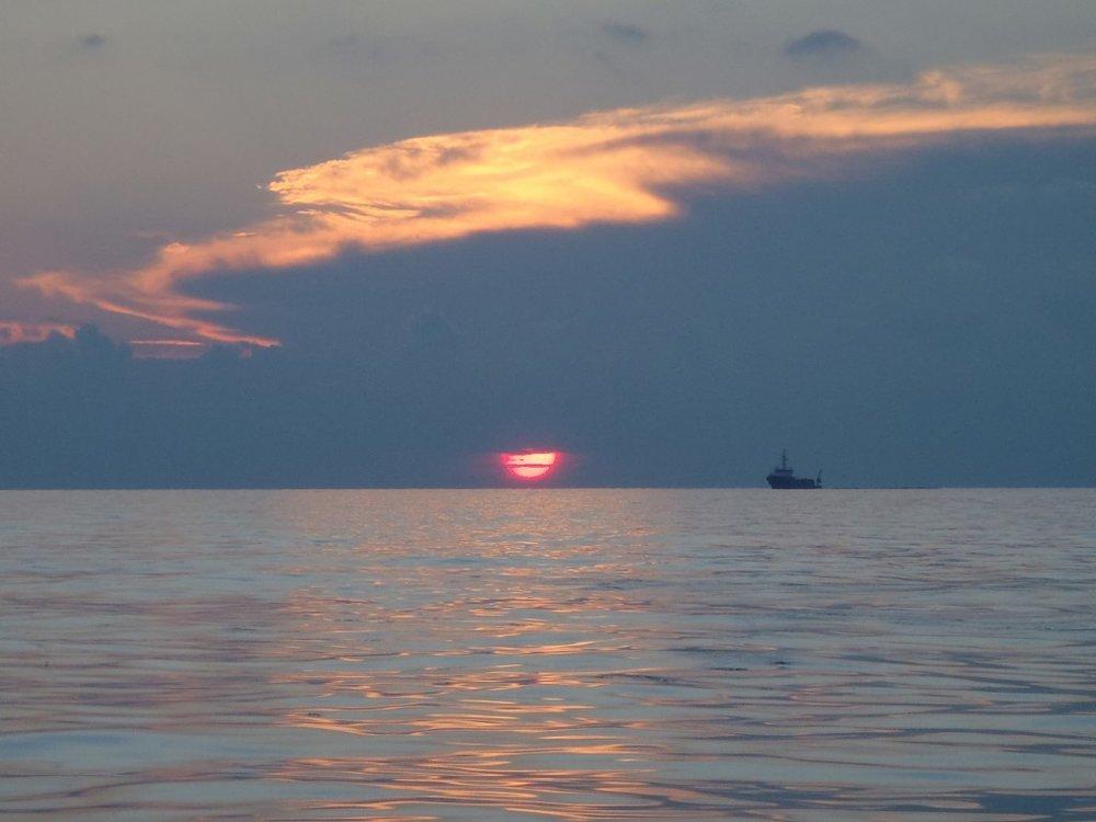 Sunset behind a skimmer boat