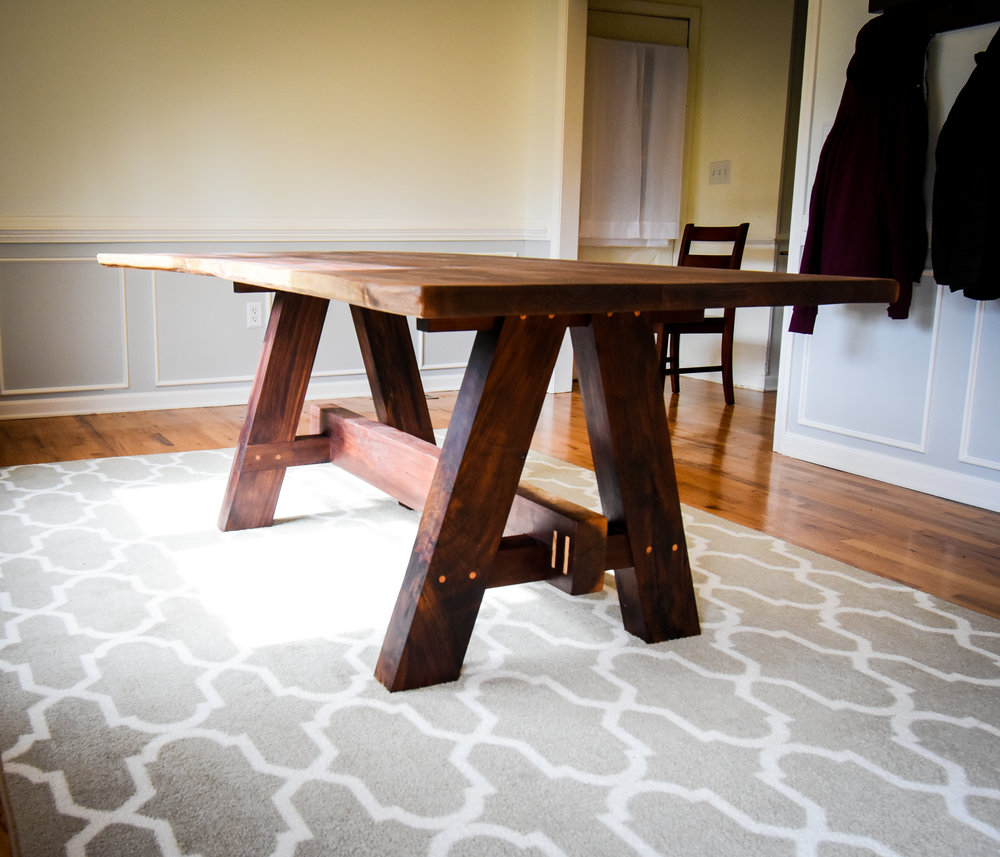 The table top is made from a walnut slab with an additional two walnut boards. Each knot and crack were filled with epoxy. Each crack has a circular oak inlay in place to stop it from spreading further down the top.