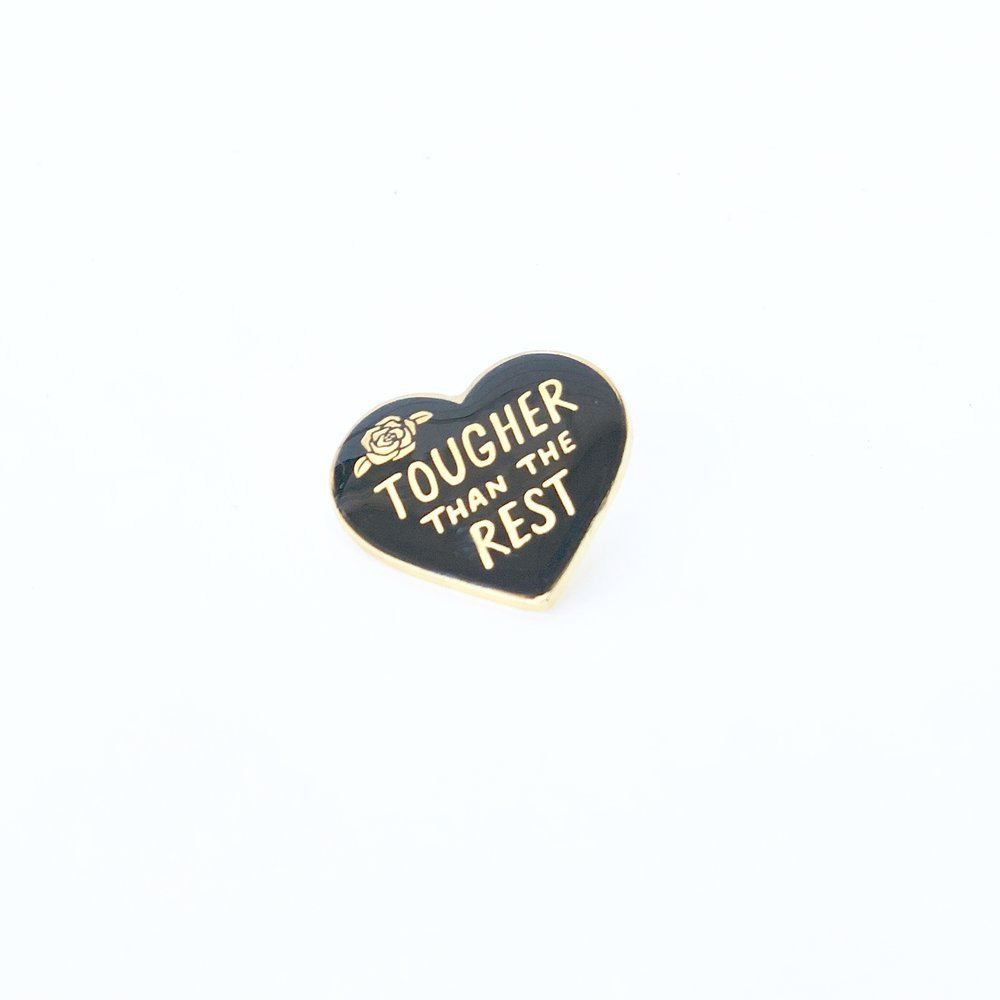 """Black enamel pin with the saying """"tougher than the rest."""""""