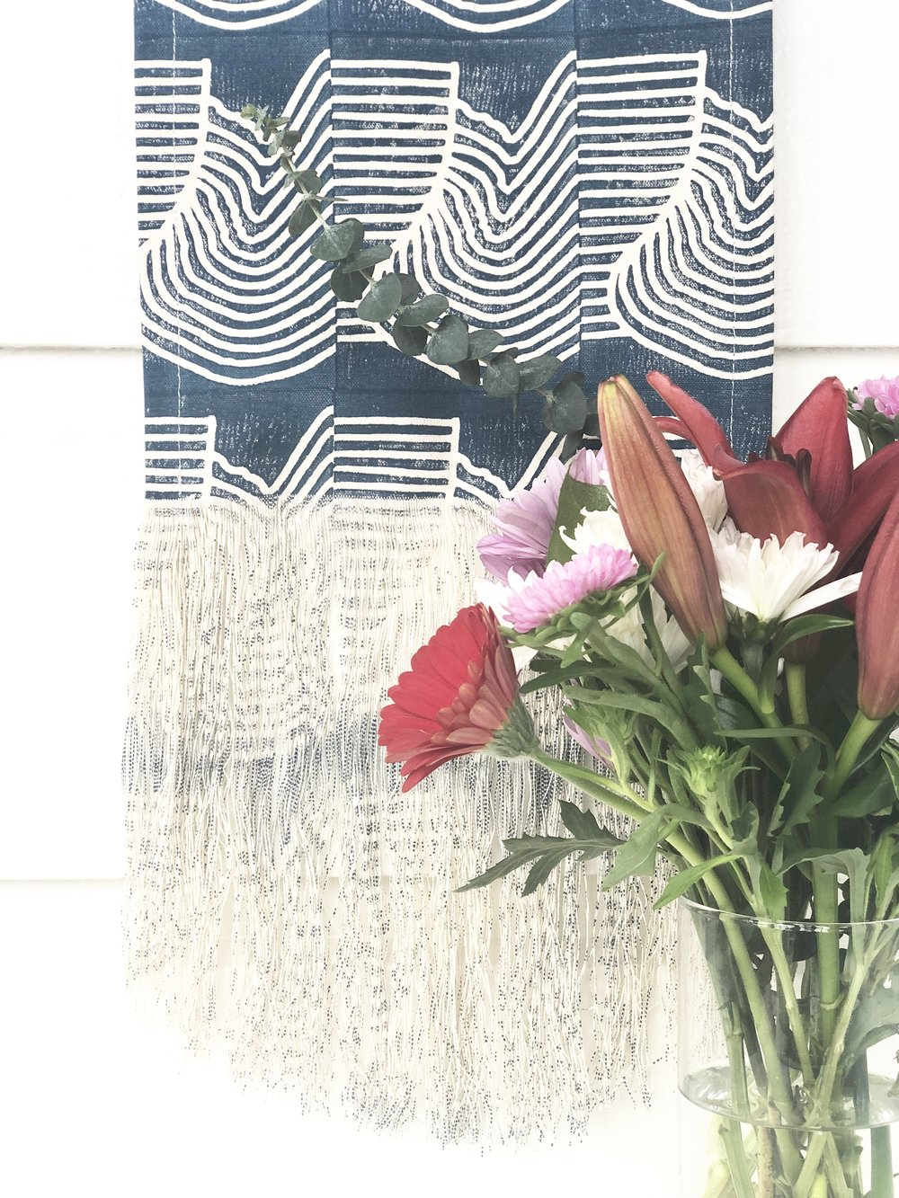 A vase of flowers in front of a wall hanging by  Julia Canright .