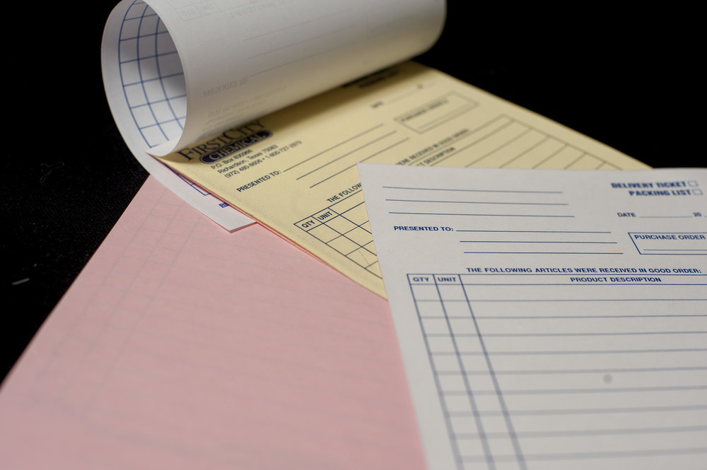 Custom-printed carbonless forms with white, yellow, and pink pages.