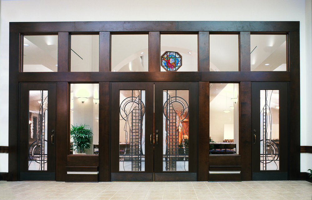 Entry doors harmonize thematically with the windows inside the church.