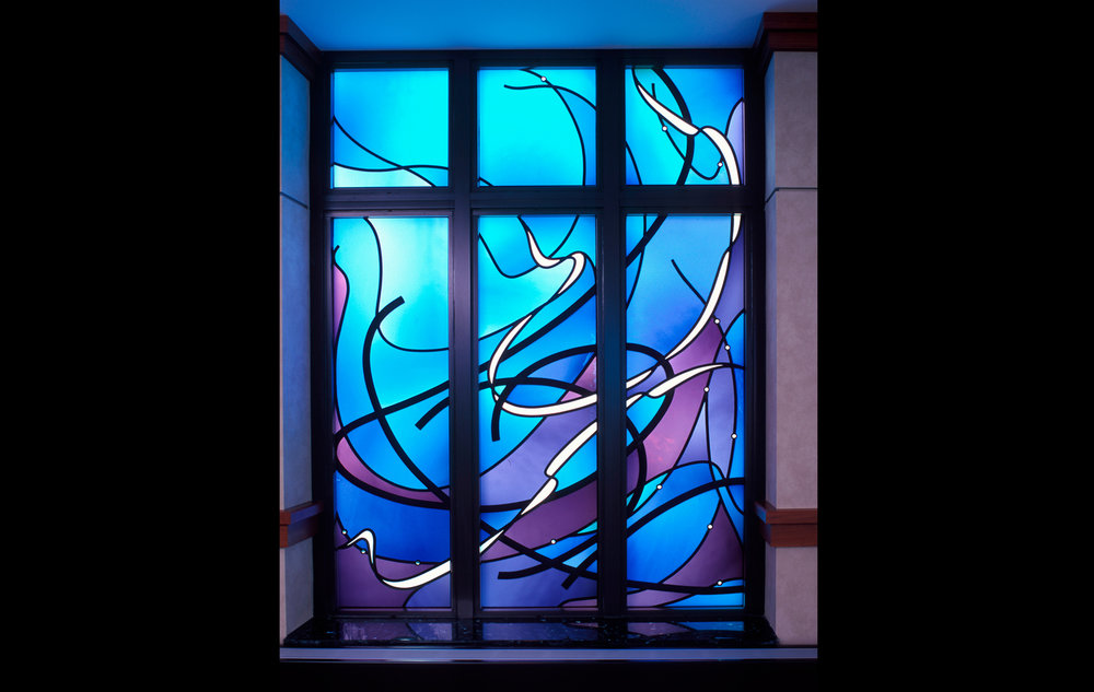 """Ruah"" Window:  With an all embracing, but very gentle, sweep of color and movement, this window speaks of Ruah, the ""Breath of God."" This soothing voice surrounds us, is always with us. It is so very gentle, yet awesomely powerful, just as the air is both breeze and wind."