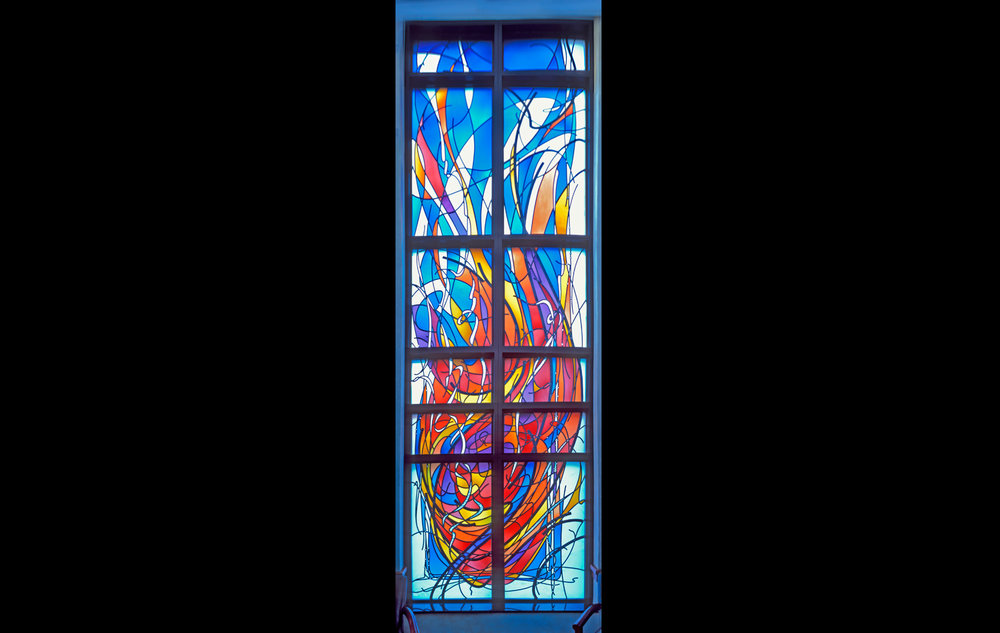 """Fire"" Window:   Fire embodies the very essence of spirituality, whether as a sacred religious symbol, or as a calming spiritual experience. Aspects of these concepts are woven into this window design. The seemingly spontaneous movement within the design suggests that the Holy Spirit is moving within and through us, empowering us with its presence. The vertical movement of line and color guides our eyes heavenward, reminding us to take our concerns to God in prayer."