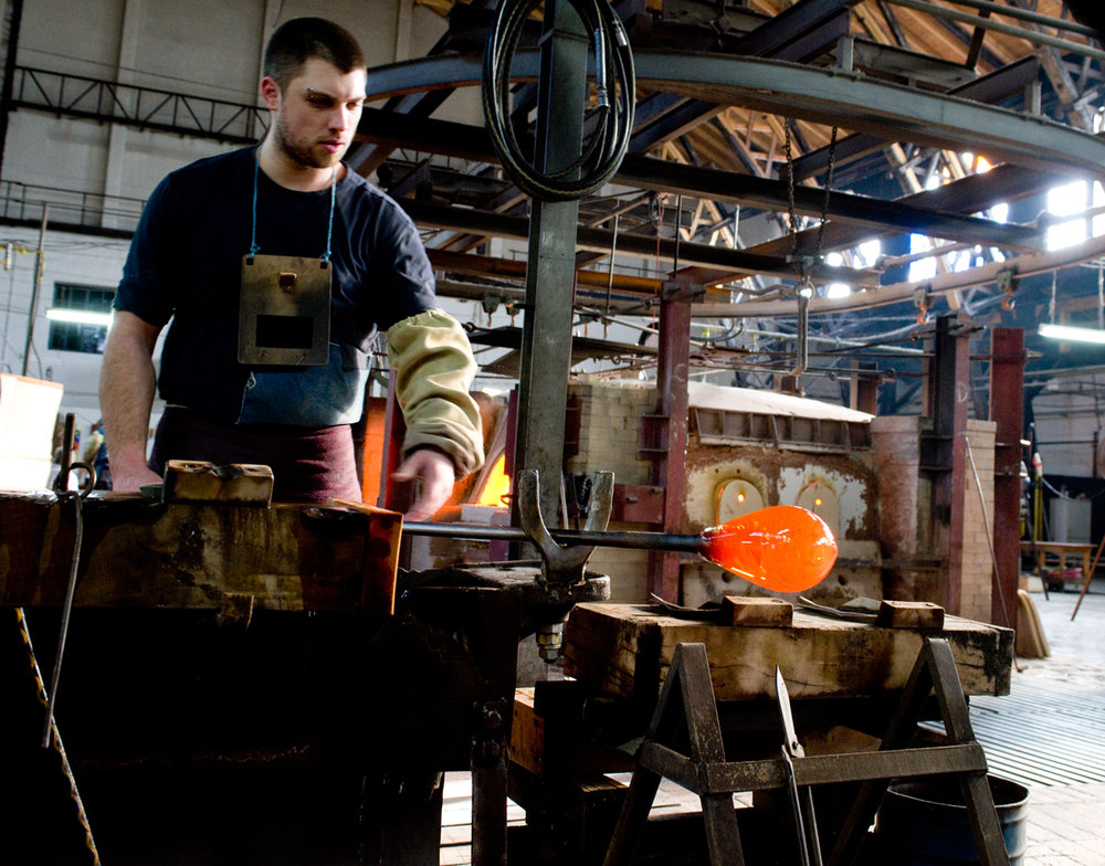 Worker shapes the glass gather into the perfect shape.
