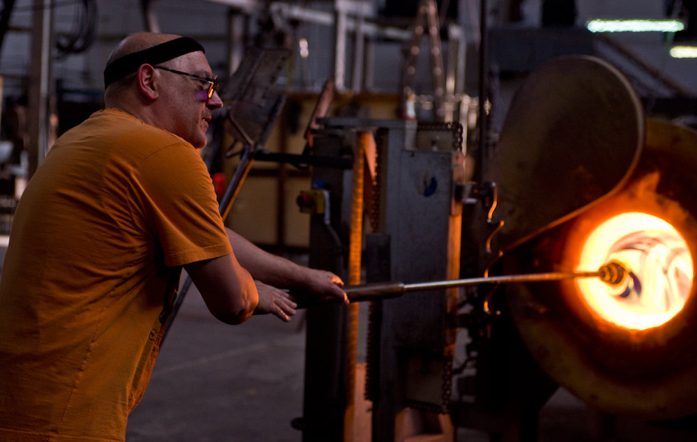 The Master Glass Blower heats the gather to near a molten state.
