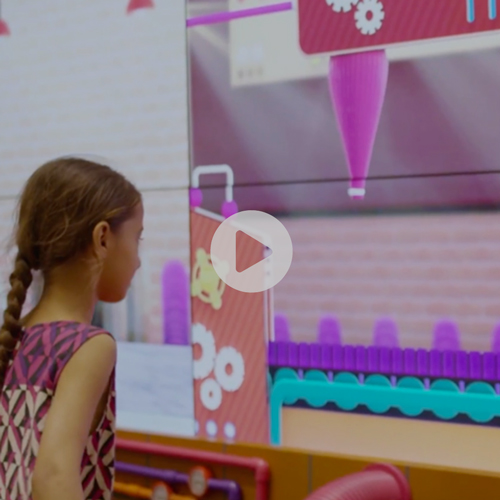 Baking Cupcakes Interactive Game at Lucky One Mall in South Asia, 2018 - A 24 feet wide media wall corridor which is composed of 3 screens, is housing the experience of baking a cupcake. Via augmented reality and gamification effects, provided by the FXMill Software Suite, the cupcake producer Peek Freans attracts huge attention to their shop and substantially increases their ROI. The results are impressive: 20.000 interactions, across 320 plus screens nationwide, reaching 8 milllion people across Pakistan