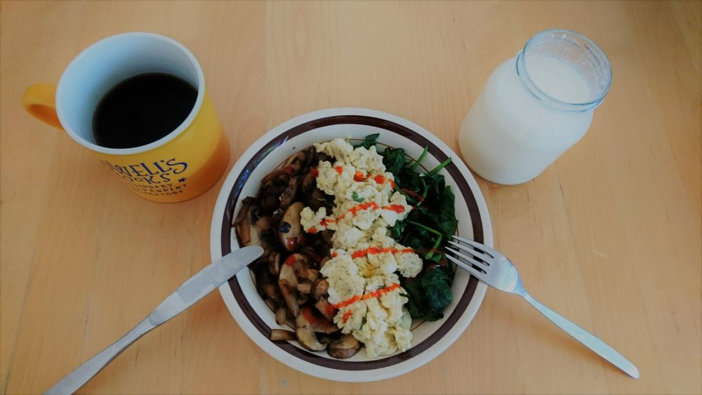 Scrambled eggs with onions, mushrooms, and spinach topped with some sriracha sauce. Additionally, a coffee and a self-made Kefir