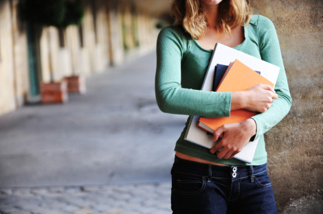 Close up of a female university student holding books and a laptop