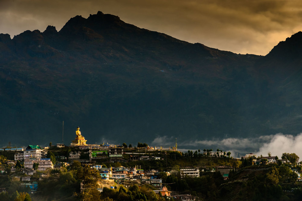 First beam of sun on Buddha statue facing east in Tawang