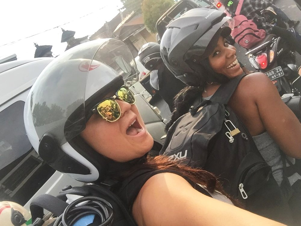Us in Bali traffic, on a motorbike, with about 50lbs on our back of retreat swag!