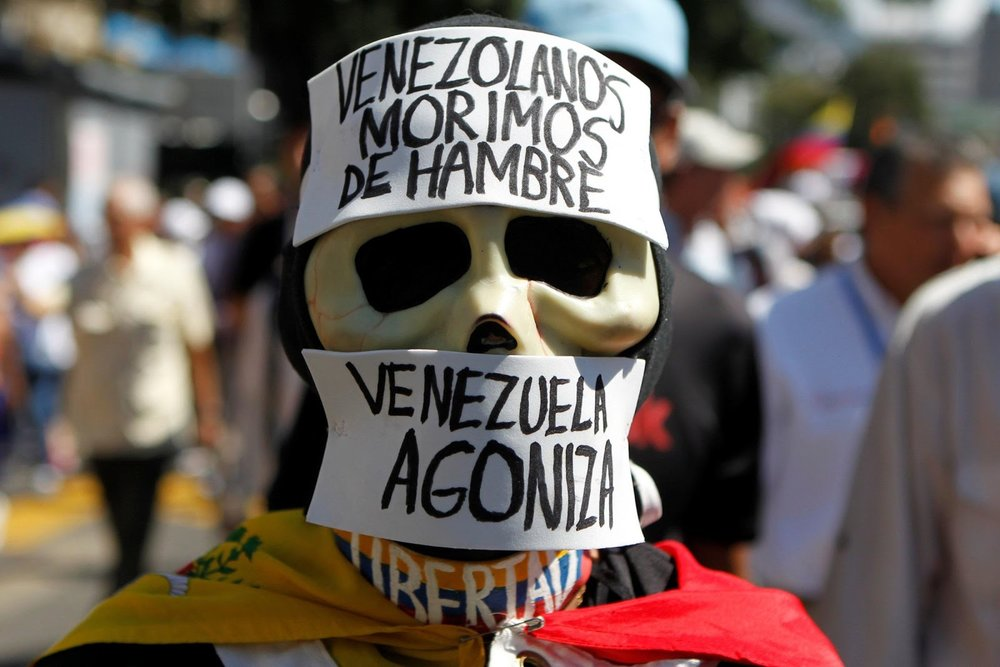"Opposition supporter wearing a costume at a rally against Maduro's governance that says, ""Venezuelans we die of hunger. Venezuela agonizes"".                    Image Credit: Christian Veron, Business Insider UK"