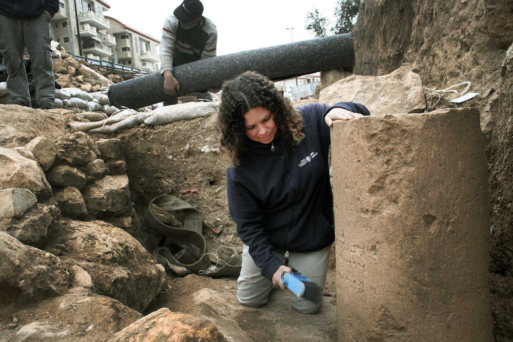 Danit Levy, Director of the excavations on behalf of the Israel Antiquities Authority, beside the inscription as found in the field. Photo: Yoli Shwartz, IAA