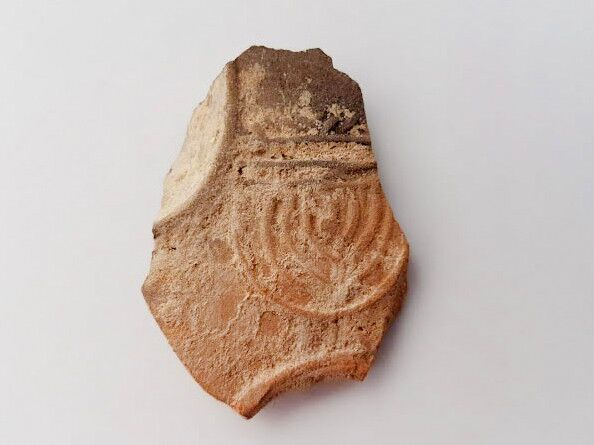 Oil lamp sherd decorated with a nine-branched menorah.  Photo: Anat Rasiuk, Courtesy of the Israel Antiquities Authority)