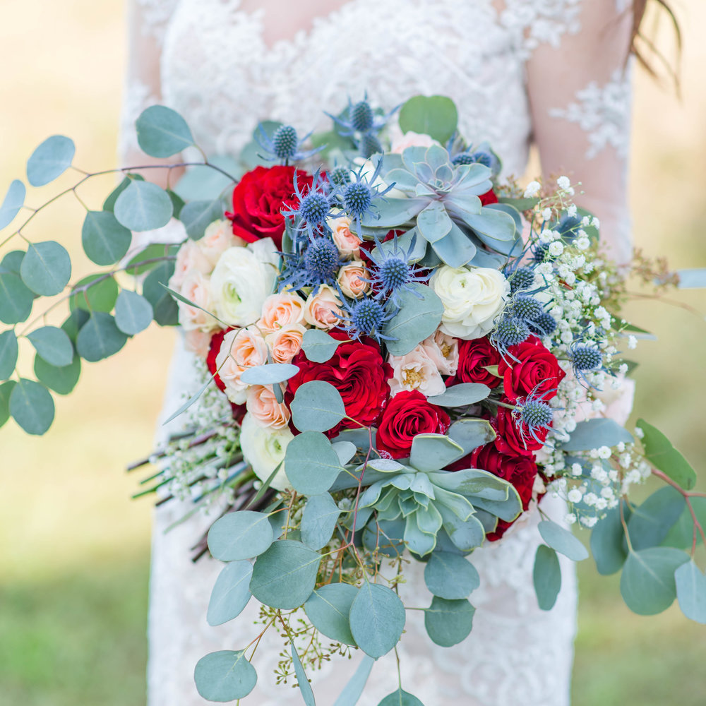 Bridal bouquet of red roses and succulents.