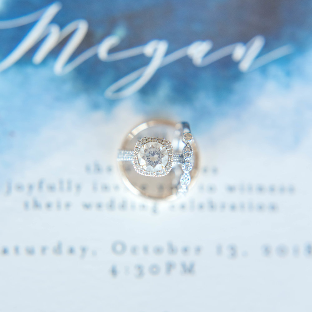 Engagement and wedding rings on a wedding invitation