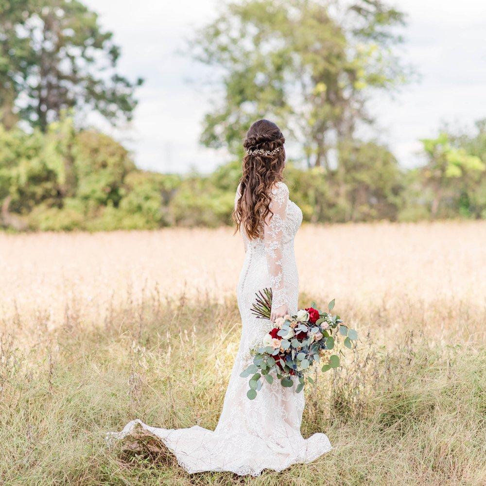 A bridal portrait in a tall grassy field.