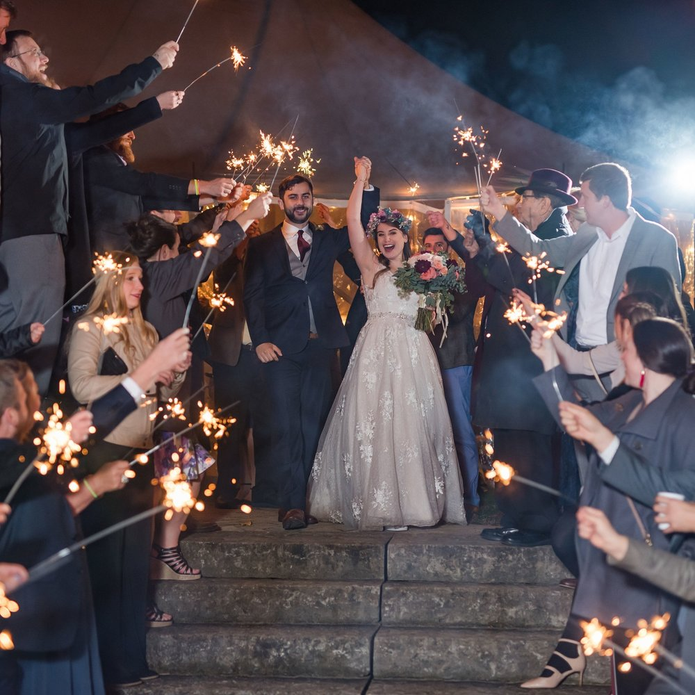 Bride and groom kiss during a sparkler exit.