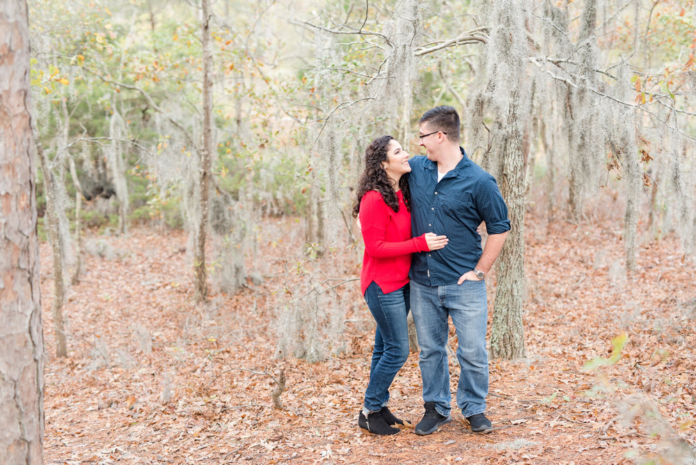 Engaged couple surrounded by Spanish moss for their fall engagement photos at First Landing State Park in Virginia Beach.