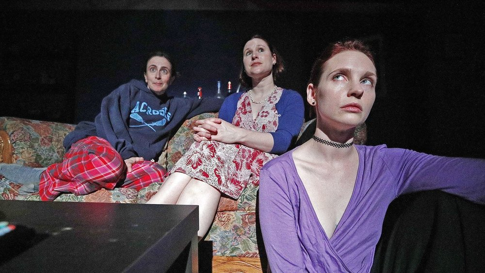 """Sisters Austin, Dallas and Baltimore, played by Jessica Blair, Leslie Connelly and Sheena Leigh, watch TV during rehearsal of a scene for the play """"Sister Cities"""" at Sidewalk Studio Theatre in Burbank. (Tim Berger / Burbank Leader)"""